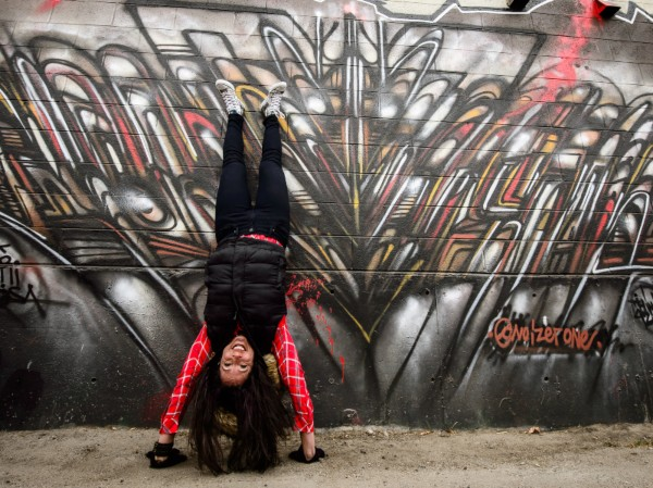 An innovative person does a handstand against a wall of graffiti