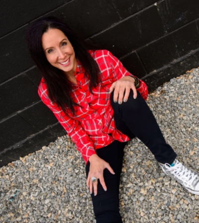 Tamara Kleinberg smiles in black jeans and red plaid shirt smile
