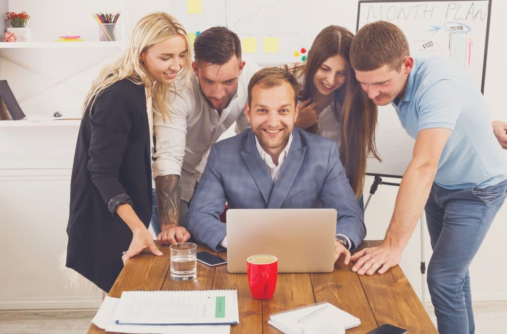 happy entrepreneur with other entrepreneurs surrounding computer